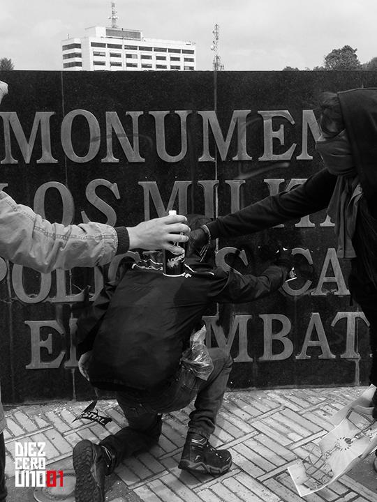 Manifestantes realizando graffiti sobre letrero en Monumento A Los Militares Caidos En Combate