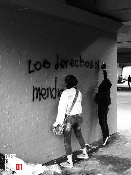 Manifestantes realizando graffiti sobre un puente en la Calle 26